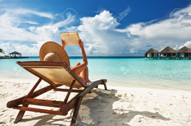 19144404-young-woman-reading-a-book-at-the-beach-stock-photo
